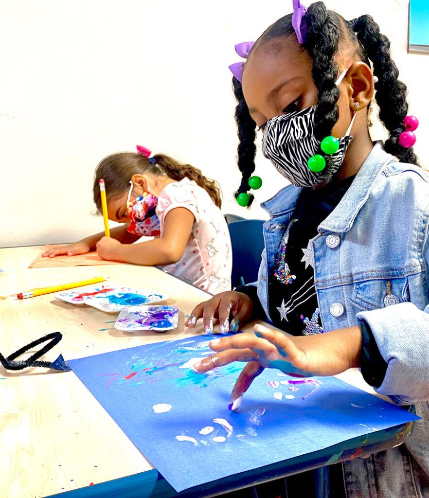 Preschool student working on finger painting activity